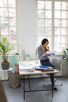 Woman with cup of coffee looking at paper at desk in office - FKF03022