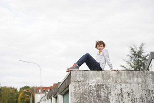 Portrait of boy sitting on garage roof - CUF37461