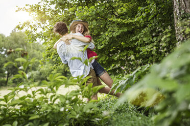 Young couple hugging and laughing in garden - CUF37479