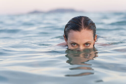 Portrait of woman partly submerged in sea, Sardinia, Italy - CUF37494