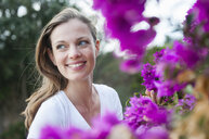 Portrait of mid adult woman next to purple blossom, Sardinia, Italy - CUF37503