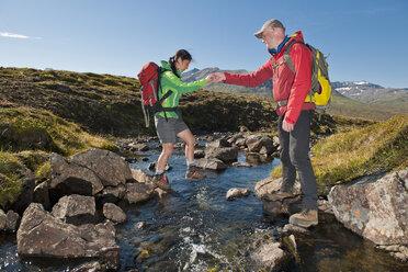 Mature hiking couple crossing river on rocks, Breidvik, Borgafjordur East, East Iceland - CUF37512