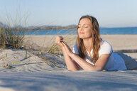 Mid adult woman lying on soft sandy beach - CUF37533