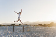 Mid adult woman jumping on beach - CUF37536