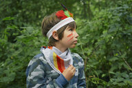 Boy dressed up in face paint and playing in forest - CUF37548