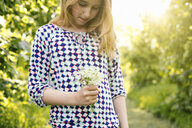 Girl daydreaming whilst looking at bunch of wildflowers - CUF37605