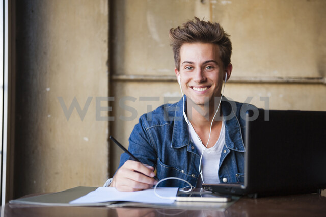 Portrait of young male student sitting at cafe table using laptop and listening to earphones - CUF37617 - Daniel Ingold/Westend61