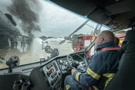 Firemen in cab of fire engine at airport training facility - CUF37632