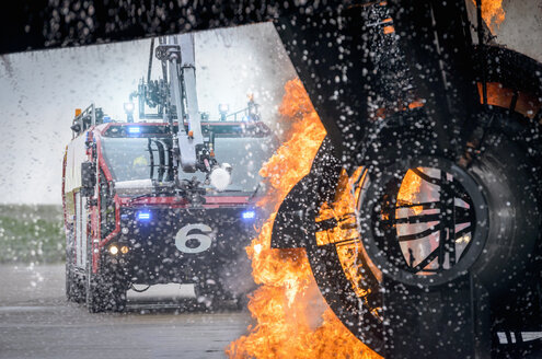 Fire engine spraying water on simulated fire at airport training facility - CUF37635