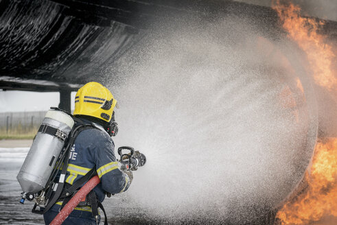 Fireman spraying water on simulated aircraft fire at training facility - CUF37638