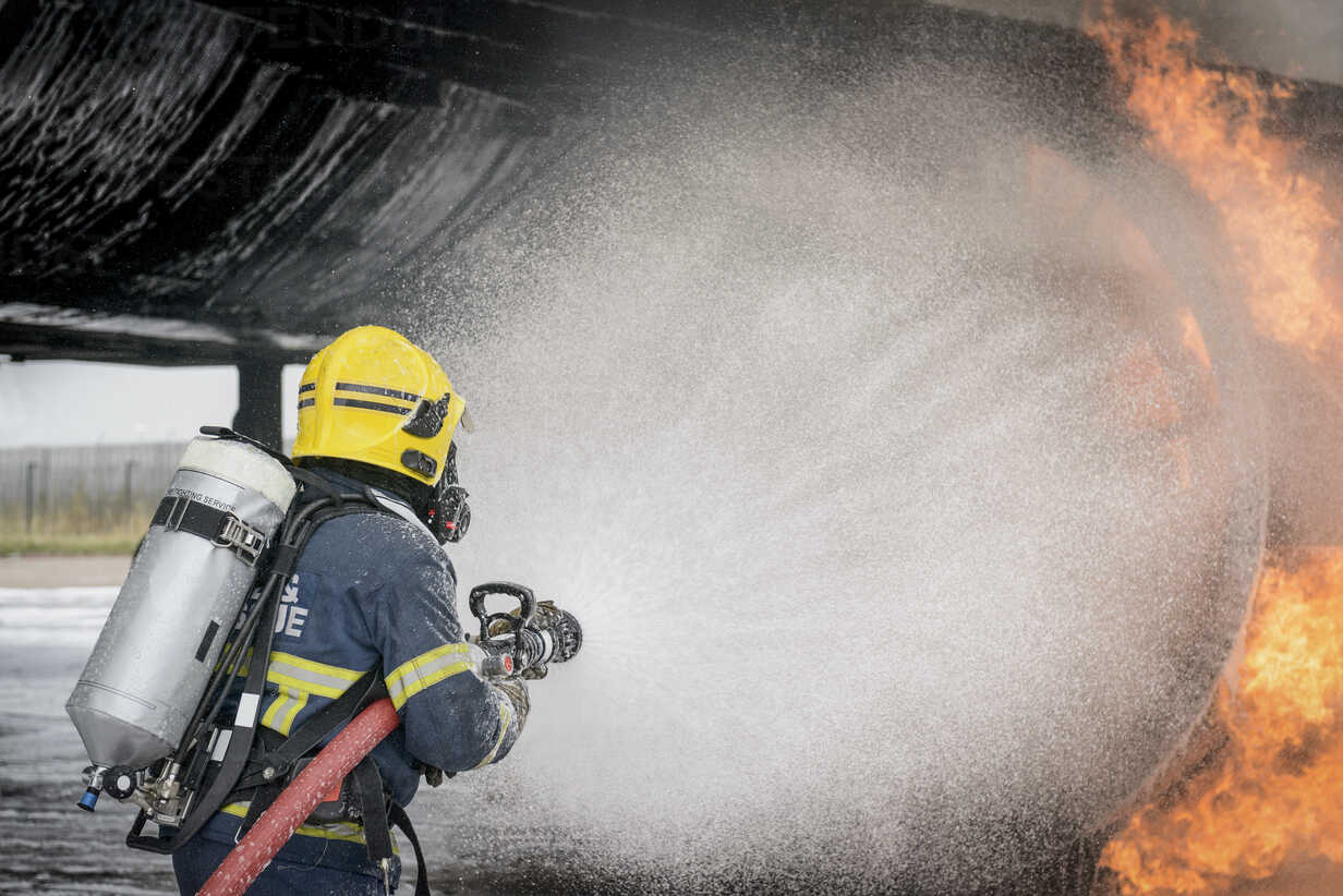 Fireman spraying water on simulated aircraft fire at training facility - CUF37638 - Monty Rakusen/Westend61