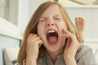 Girl with eyes closed screaming in holiday apartment - CUF37650