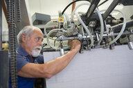 Factory worker working machinery - CUF37659