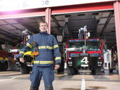 Portrait of fireman in front of fire engines in airport fire station - CUF37689