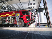 Fireman carrying equipment to fire engine in airport fire station - CUF37692