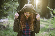 Teenage girl in hooded top in forest - CUF37713