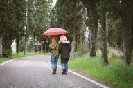 Rear view of mother and teenage daughter on rural road - CUF37716