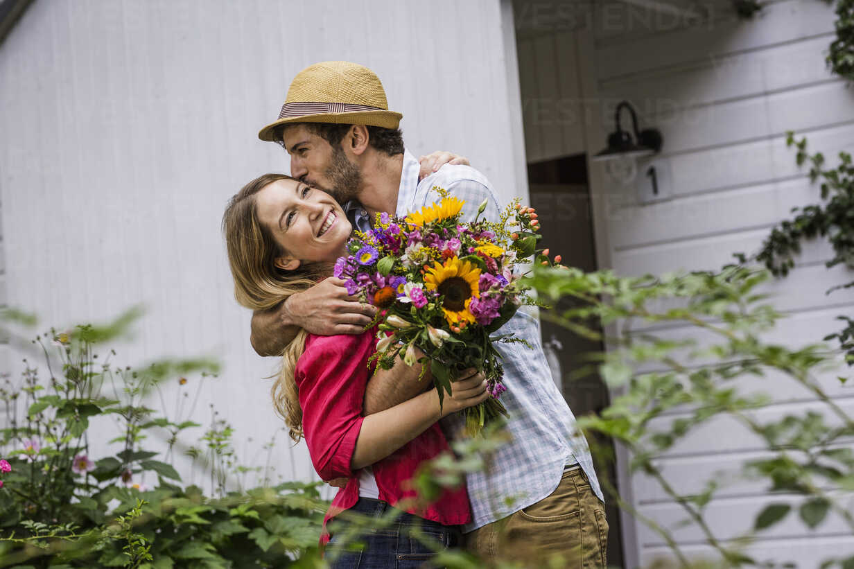 Young Couple With Bunch Of Flowers Hugging In Garden Cuf37728 Matelly Westend61