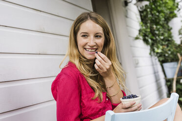 Young woman eating blueberries in front porch - CUF37734