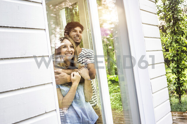 Young couple looking out of patio window - CUF37737