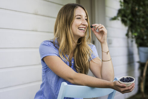 Young woman eating blueberries in front porch - CUF37740