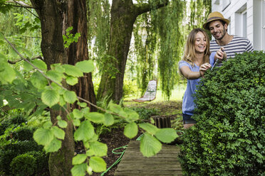 Young couple in garden pruning bush - CUF37743
