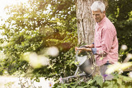 Mature man watering plants in garden - CUF37749
