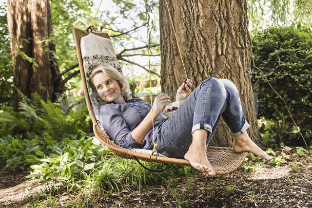Mature woman relaxing with bowl of cherries on hammock - CUF37761