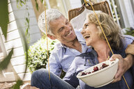 Husband and wife relaxing with bowl of cherries on hammock - CUF37764