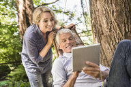 Wife watching husband using digital tablet on hammock - CUF37767