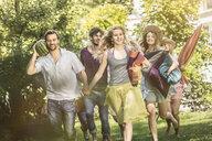 Friends walking in garden with picnic - CUF37770