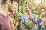 Friends in garden holding watermelon - CUF37782