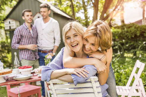 Group of friends at garden party,two female friends embracing - CUF37818