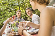 Group of friends enjoying garden party - CUF37821