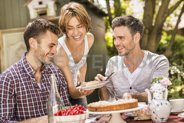 Group of friends enjoying garden party, young woman holding plate with dessert - CUF37824