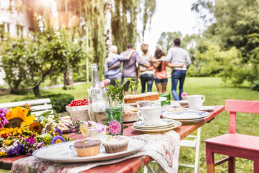 Group of friends walking away with arms around each other, garden party table with food in foreground - CUF37830
