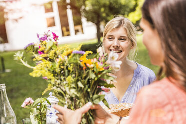 Two female friends in garden, looking at bunch of flowers - CUF37833