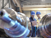Engineers inspecting finished steel rollers in engineering factory - CUF37842