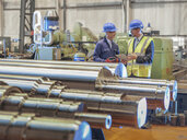 Engineers inspecting finished steel rollers in engineering factory - CUF37845