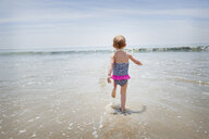 Female toddler running into the sea - ISF14581