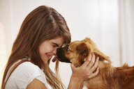 Young woman having face licked by pet dog - ISF14638