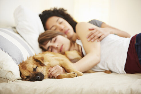 Young female couple and pet dog sleeping on bed - ISF14641