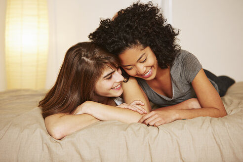 Affectionate young female couple lying on bed - ISF14644