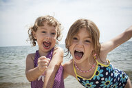 Portrait of two sisters pulling faces on beach at Falmouth, Massachusetts, USA - ISF14654