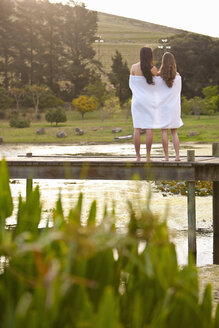 Two young women standing on river pier wrapped in blanket - ISF14740