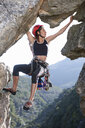 Young female rock climber balancing on rock face - ISF14749