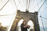 Young woman taking self portrait on Brooklyn bridge, New York, USA - ISF14890