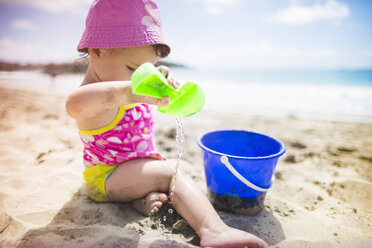 Baby playing on sandy beach with bucket and spade - ISF14902