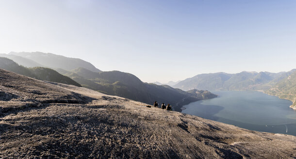 Three young female hikers taking a break on rock, Squamish, British Columbia, Canada - ISF15001
