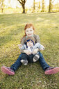 Portrait of girl and baby brother on grass in park - ISF15031